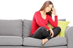 Ledset sammanträde för ung kvinna på en modern soffa royaltyfri fotografi