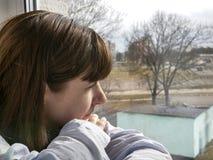 Ledset seende fönster för attraktiv ung brunettkvinna, närbild arkivfoto