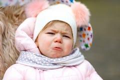 Ledset skriande hungrigt behandla som ett barn flickasammanträde i pramen eller sittvagnen på kall dag fotografering för bildbyråer
