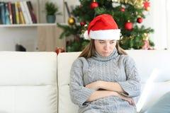 Ledset tonårigt sammanträde på en soffa i jul tajmar hemma royaltyfri fotografi