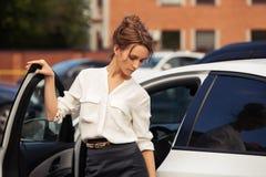 Ledset ungt anseende för modeaffärskvinna bredvid hennes bil royaltyfria bilder