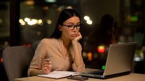 Ledset ungt kvinnligt glas?gon som direktanslutet s?ker jobb, brist av id?er, arbetsutmattning arkivfoto