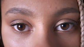 Ledsna bruna ögon av en afrikansk flicka med dreadlocks stock video