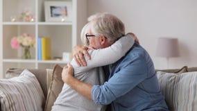 Ledsna höga par som hemma kramar lager videofilmer