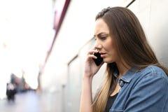 Ledsna kvinnasamtal på telefonen i gatan royaltyfria foton