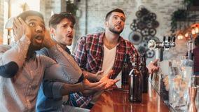 Ledsna manliga vänner som håller ögonen på fotboll på stången royaltyfri bild