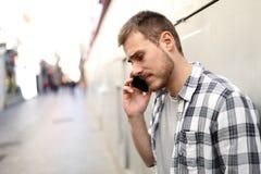 Ledsna mansamtal på telefonen i en enslig gata arkivbild