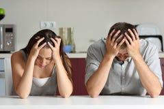 Ledsna och bekymrade par i köket Arkivfoto