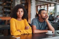 Ledsna och ilskna unga par i kafé royaltyfria bilder