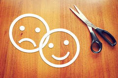 Ledsna och lyckliga emoticons som göras av papper på skrivbordet Royaltyfri Fotografi