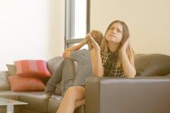 Ledsna par efter argument eller upplösning som inomhus sitter på en soffa i vardagsrummet i ett hus royaltyfria foton