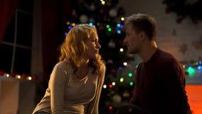 Ledsna par som sitter under julgranen, bortskämd ferie, förhållandeproblem fotografering för bildbyråer