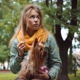 Ledsna unga kvinnor med den väntande pojkvännen för hunden i stad parkerar Royaltyfria Bilder