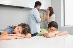 Ledsna unga ungar medan föräldrar som grälar i kök Royaltyfria Foton
