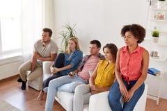 Ledsna vänner som hemma håller ögonen på tv Arkivbilder
