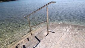 Ledstång för att simma och trappa på stranden av havet Stålsätta ledstången, simning, det blåa havet, sjösidan, vågor, sommar, lo arkivfilmer