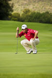 Lee Westwood. Reading lie of the green, takes aim, before putting Royalty Free Stock Images