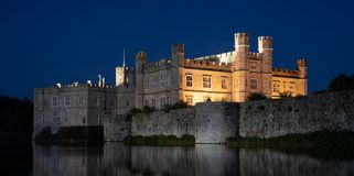 Leeds Castle in Kent UK, illuminated at night and reflected in the surrounding water.