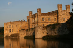 Leeds castle with moon in the sky. The sun doing down on leeds castle with moon in the sky royalty free stock image