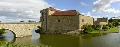 Leeds castle south side , Maidstone, England. View of the southern side of medieval castle and its moat,  shot in bright light under a cloudy sky Stock Photos