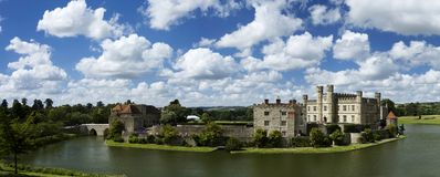 Leeds Castle on a Summers day. Panoramic photo of Leeds Castle reflected in the still waters of the surrounding moat. A deep blue summer sky is full of typical royalty free stock images
