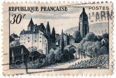 An old blue french postage stamp with an image of the town of arbois. Leeds, England - April 20 2018: an old blue french postage stamp with an image of the town Stock Image