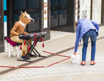 LEEDS, UK - 24 July 2015.  Man with a horses head playing the ke. Yboard and busking for money.  Lady putting money into busker, begger, performer's hat Stock Images