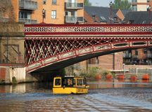 A yellow water taxi boat passing under crown point bridge over the river aire in leeds. Leeds, west yorkshire, england 18 april 2019: a yellow water taxi boat stock photography