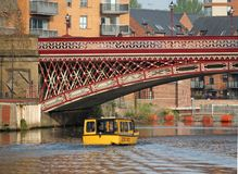 A yellow water taxi boat passing under crown point bridge over the river aire in leeds. Leeds, west yorkshire, england 18 april 2019: a yellow water taxi boat royalty free stock photos