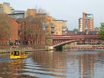 A yellow water taxi boat passing under crown point bridge over the river aire in leeds. Leeds, west yorkshire, england 18 april 2019: a yellow water taxi boat stock photos