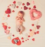 Leef in liefde Familie Kinderverzorging Klein meisje onder rode harten Snoepje weinig baby Het nieuwe leven en geboorte Liefde Po stock foto