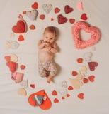 Leef in liefde Familie Kinderverzorging Klein meisje onder rode harten Snoepje weinig baby Het nieuwe leven en geboorte Liefde Po stock foto's