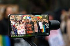 Leef stroom bij smartphone, tijdens Protestactie om solidariteit met Chechnya's LGBT te tonen stock afbeelding