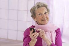 Leeftijd en mensenconcept - sluit omhoog van gelukkige hogere vrouw met smartphone thuis Stock Afbeeldingen