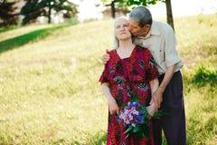 Leeftijdspaar in de handen van de liefdeholding op een gang in het park in de zomer stock foto