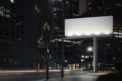 Leeg aanplakbord bij nacht met de stad op achtergrond het 3d teruggeven Stock Foto