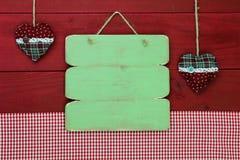 Leeg antiek groen houten menuteken met vakantieharten en rood gingangtafelkleed Royalty-vrije Stock Afbeeldingen