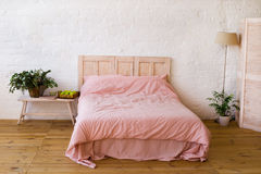 Leeg bed met roze hoofdkussens en roze dekking in de slaapkamer royalty-vrije stock afbeeldingen