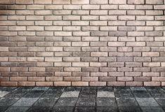 Leeg binnenlands perspectief - bakstenen muur en voetpadsteengrond Stock Fotografie