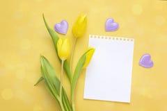 Leeg blad van notitieboekje en gele tulpen op een gele achtergrond Stock Foto