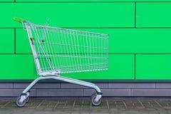 Leeg boodschappenwagentje op groene achtergrond De kar voor aankopen, sluit omhoog Verkoop, kortingen Het winkelen stock fotografie