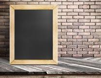 Leeg bord op diagonale houten lijst bij rode bakstenen muur, Temperaturen Stock Afbeeldingen