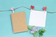 Leeg bruin notitieboekje en Witboek de kaart met rood hart ontwerpt klem met bloem op blauwe achtergrond stock foto