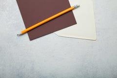 Leeg bruin vierkant stuk van document, beige envelop en potlood op uitstekende witte achtergrond Lege ruimte voor tekst De idylle royalty-vrije stock foto's