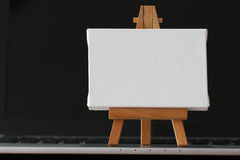 Leeg canvas en houten schildersezel op laptop computer Stock Foto's