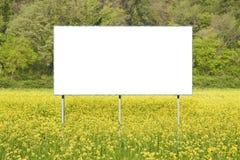 Leeg commercieel reclameaanplakbord dat in een landelijke scène tegen een geel bloemrijk gebied wordt ondergedompeld - beeld met  royalty-vrije stock foto