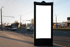 Leeg de straataanplakbord die van het advertentiemodel zich dichtbij een weg met het bewegen van vage auto's - Lange blootstellin stock foto's