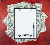 Leeg die document blad in klembord op centrum van gelddollar en houten achtergrond, bedrijfsconcept en informatiemodel wordt gepl Royalty-vrije Stock Afbeeldingen