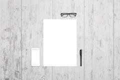 Leeg document en mobiele telefoon op bureau Hoogste mening met glazen en pen naast stock foto's