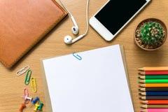 Leeg document, kleurenpotlood, en slimme telefoon op houten bureau Stock Afbeelding